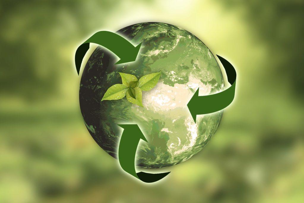 Kuvituskuva, jossa vihreällä taustalla maapallo, jonka ympäri menee kolme vihreää nuolta.