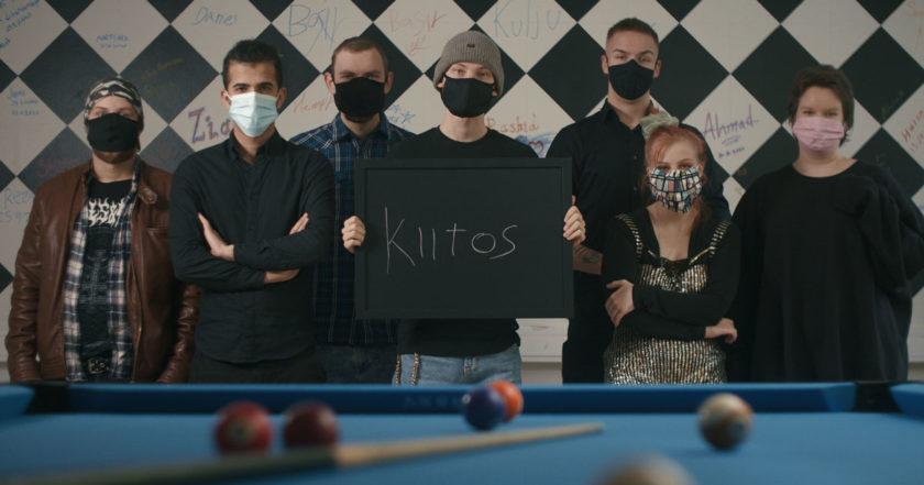 Kuvassa nuoria ihmisiä maskit kasvoillaan pitäen kylttiä, jossa lukee kiitos.