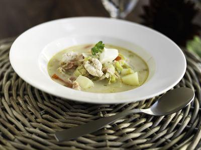 Kuvassa ruskean koripöydän päällä valkoinen lautanen, jossa kalakeittoa. Lautasen edessä lusikka.