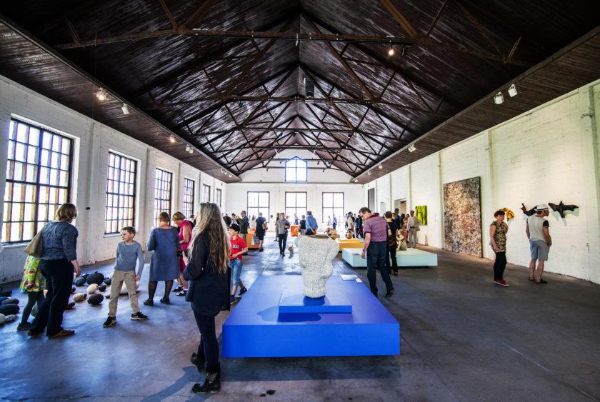 Kuvassa iso näyttelysali, jossa tumma lattia ja katto ja vaaleat seinät. Vasemmalla puolella ikkunat, keskellä lattiaa sininen taso jolla taidetta. Tilassa paljon ihmisiä katselemassa taideteoksia.