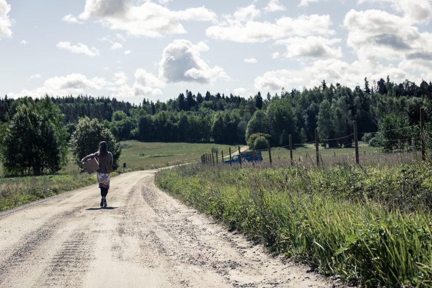 Kuvassa suomalainen maalaismaisema. Hiekkatie keskellä vihreää nurmea, horisontissa vihreää metsää ja sininen taivas.