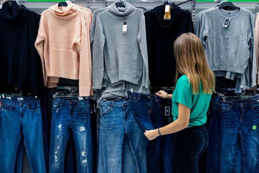 Kuvituskuvassa seinällä rekeissä farkkuja ja puuvillapaitoja. Edessä nuori, pitkähiuksinen nainen selkä katsojaan päin katselee vaatteita.