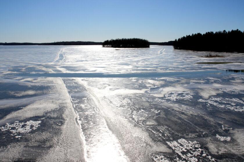 Aurinkoinen talvikuva jäässä olevasta järvestä.